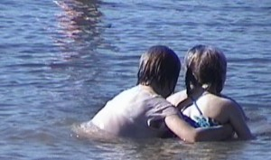 A boy and girl swimming in a blue lake