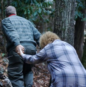 An gray haired man dressed in blue helps a gray haired woman climb a trail through the woods